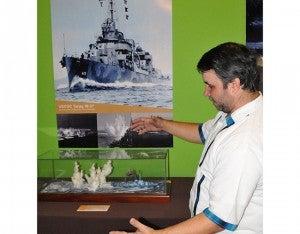 Junto a cada diorama Roberto Danilov tiene poster con las escenas que está recreando. En esta por ejemplo se ve las columnas de agua que saltan junto a un barco que es bombardeado desde el cielo.