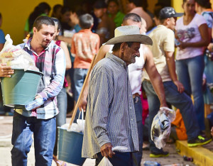 """Mexican people displaced by violence and operations against drug trafficking wait for food in front of a temporary shelter in the Cosala town, Sinaloa State on October 17, 2015.  Mexican authorities increased their efforts to stop the drug kingpin Mexican Joaquin Guzman, aka """"El Chapo"""" who was injured recently escaping from a special forces operative in the region. AFP PHOTO/RONALDO SCHEMIDT"""